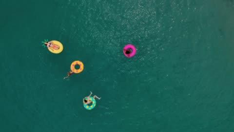 friends having fun on floaties in water - floating on water stock videos & royalty-free footage