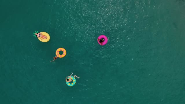 friends having fun on floaties in water - rubber ring stock videos & royalty-free footage