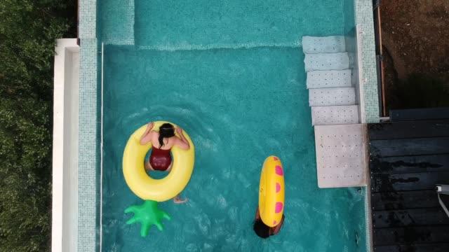vídeos y material grabado en eventos de stock de amigos que se divierten en anillos inflables en la piscina - lugar turístico