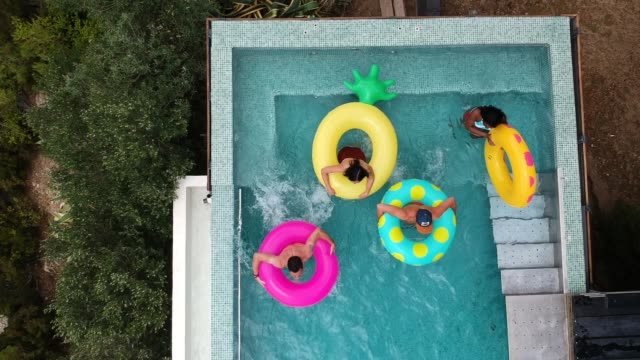 friends having fun on inflatable rings in the pool - rubber ring stock videos & royalty-free footage