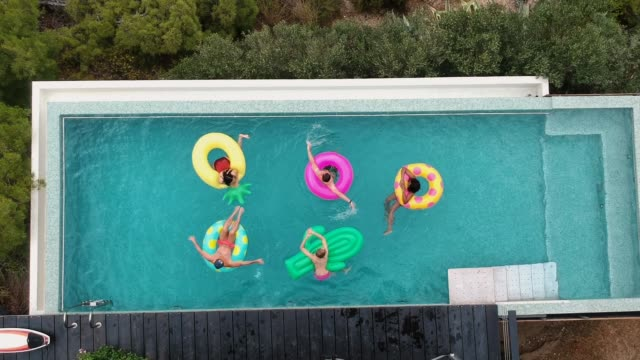 vídeos de stock, filmes e b-roll de amigos se divertindo em anéis infláveis na piscina - lago infinito