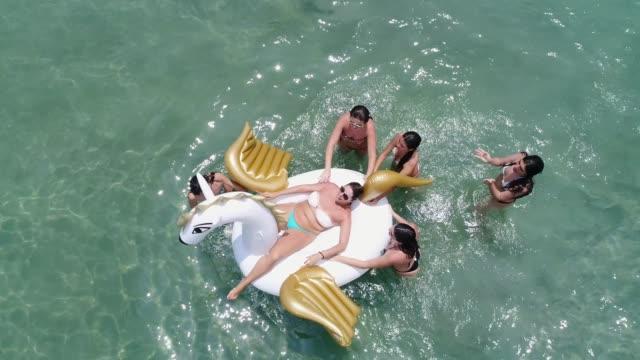 vídeos de stock, filmes e b-roll de amigos se divertindo com flutuador inflável na praia - vista aérea - beach holiday