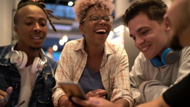 コーヒーショップで携帯電話で楽しんでいる友人 - バイラルビデオ点の映像素材/bロール