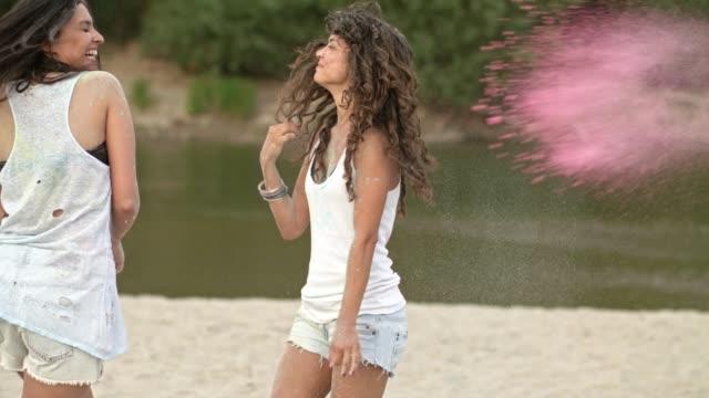 vídeos de stock, filmes e b-roll de amigos se divertindo com pigmento de tinta - areia