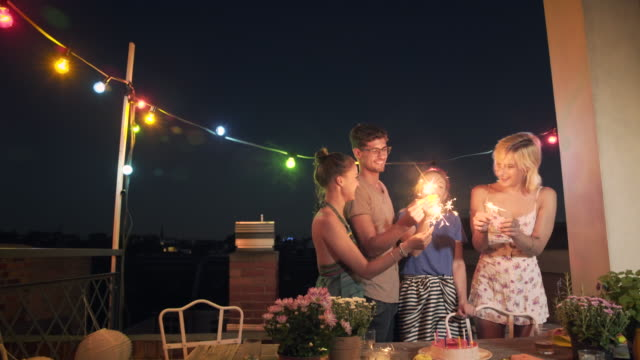 friends having fun with sparklers on an urban rooftop - kleine personengruppe stock-videos und b-roll-filmmaterial