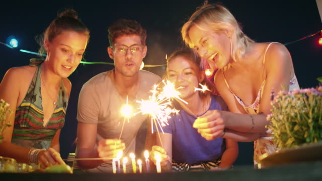 Friends having fun with sparklers on an urban rooftop