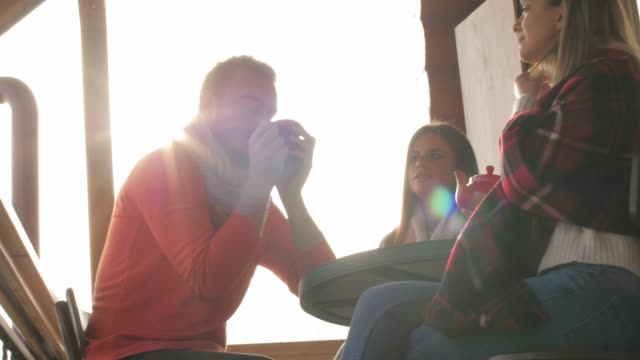 friends having tea in warm winter sunshine outdoors - patio stock videos & royalty-free footage