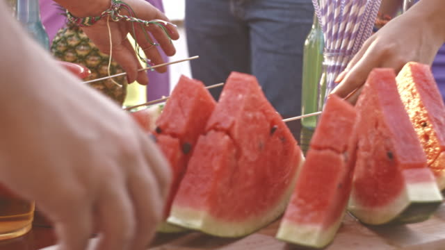 Friends having watermelon while on a party