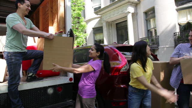 ms pan friends helping each other to unload moving truck / newark, new jersey, united states - relocation stock videos and b-roll footage