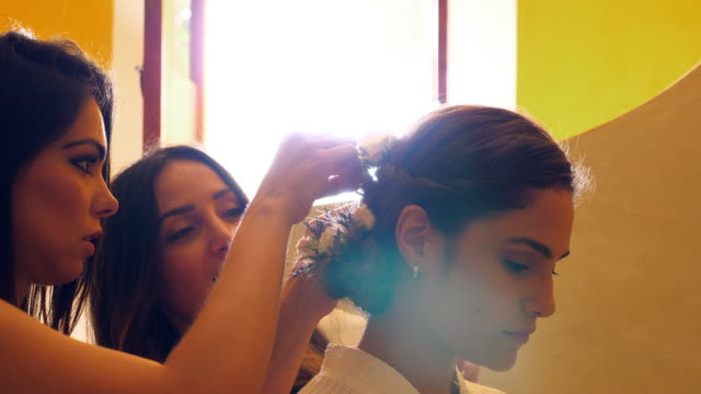 vídeos y material grabado en eventos de stock de cu friends helping smiling bride put flowers in hair in hotel room before wedding ceremony - recuerdos