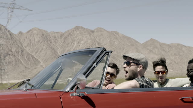 Friends high-five in classic convertible cruising down desert highway