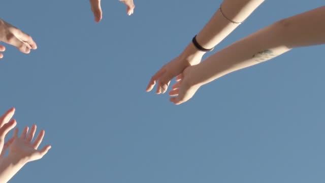 vidéos et rushes de amis retenant des mains vers le haut dans l'air - vue en contre plongée