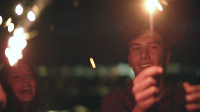 cu sm friends holding sparklers at night - small group of people stock videos & royalty-free footage