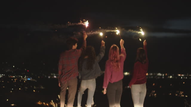 rv friends holding sparklers up in the air at night - jeans video stock e b–roll