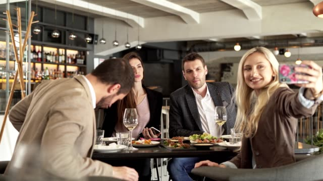 friends in a restaurant taking a selfie - silver service stock videos & royalty-free footage