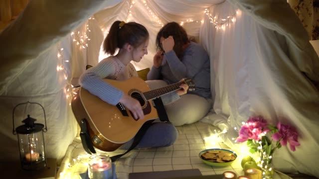 vídeos de stock, filmes e b-roll de amigos em uma tenda de lençóis à noite - violão acústico