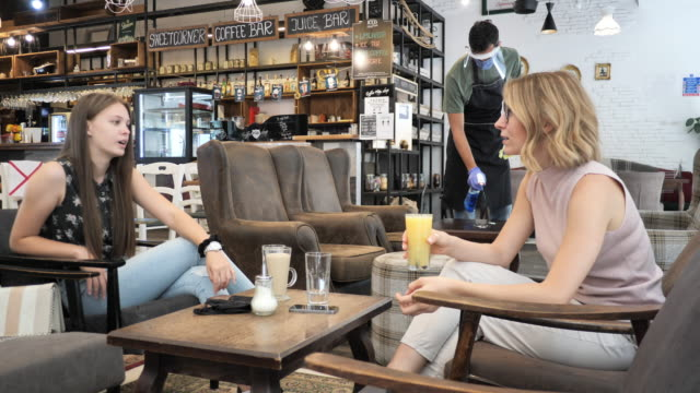 friends in cafe drinking coffee and chatting. two women sitting and keeping 6ft social distance - indoors stock videos & royalty-free footage