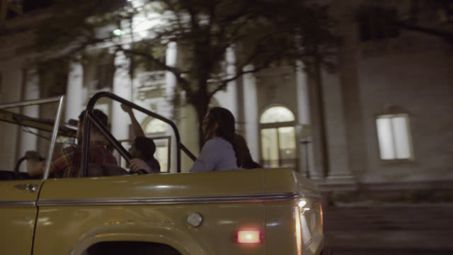 vidéos et rushes de friends in classic ford bronco speed through downtown austin, texas at night - aller tranquillement