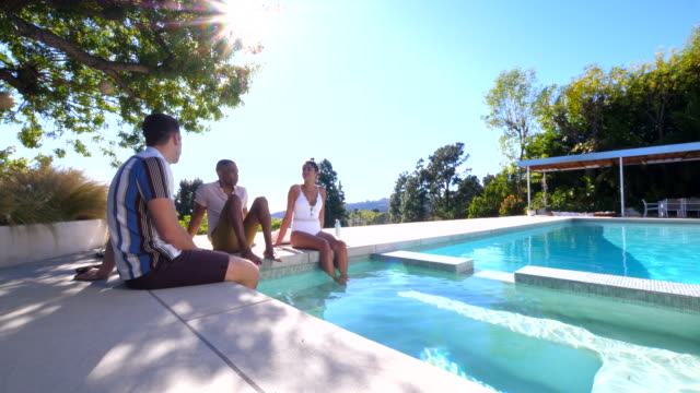 ws pan friends in discussion while relaxing by pool of vacation rental - swimming costume stock videos & royalty-free footage