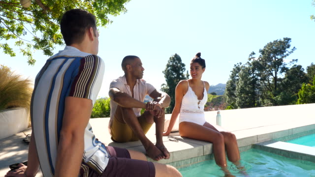 ms friends in discussion while relaxing by pool of vacation rental - swimming costume stock videos & royalty-free footage