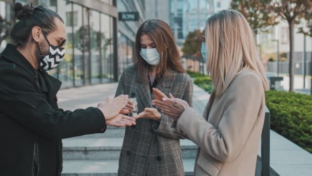 vídeos y material grabado en eventos de stock de amigos con máscaras faciales reunidos en la ciudad durante la pandemia de coronavirus. compartir desinfectante de manos - untar