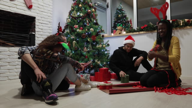friends in good mood while wrapping christmas gifts - antler stock videos & royalty-free footage