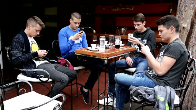 friends in the cafe using their phones