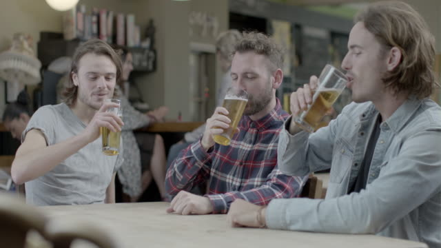friends in together in pub - pint glass stock videos & royalty-free footage