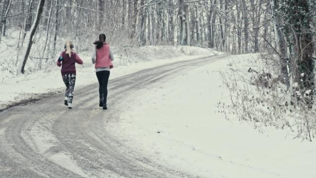 vidéos et rushes de amis, faire du jogging sur route enneigée - joggeuse