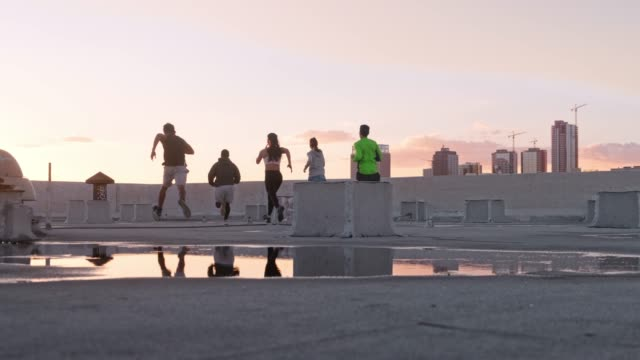 friends jogging together on rooftop in the city. - five people stock videos & royalty-free footage