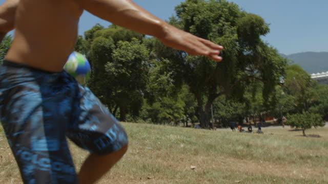 vídeos de stock, filmes e b-roll de friends juggle soccer ball on hillside overlooking world cup stadium - proeza acrobática