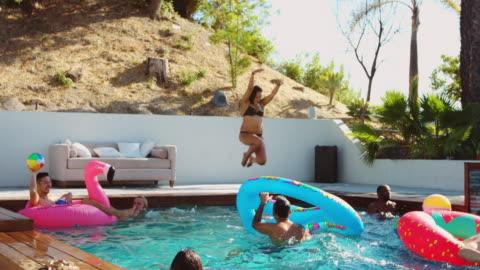 amici che si destreggiano e giocano con i giocattoli della piscina in una bellissima piscina all'aperto - swimming pool video stock e b–roll