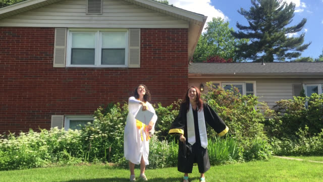 vidéos et rushes de friends jump for joy in their front yard as they celebrate graduating from college. (audio) - casquette
