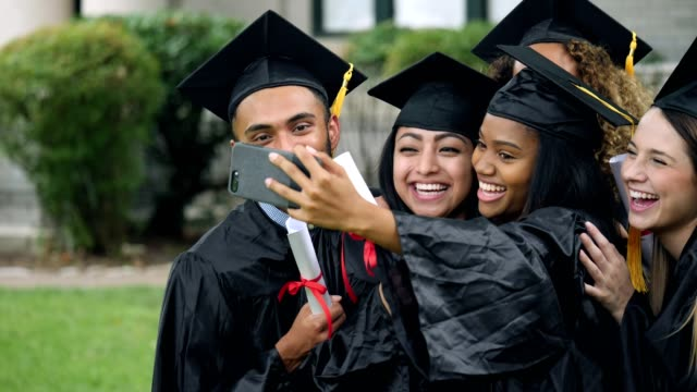 friends jump in to a self portrait of two female graduates - graduation stock videos & royalty-free footage