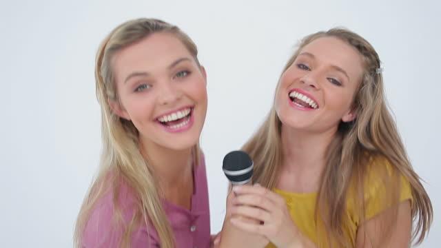vídeos y material grabado en eventos de stock de friends jumping and singing in a microphone - cinta de cabeza