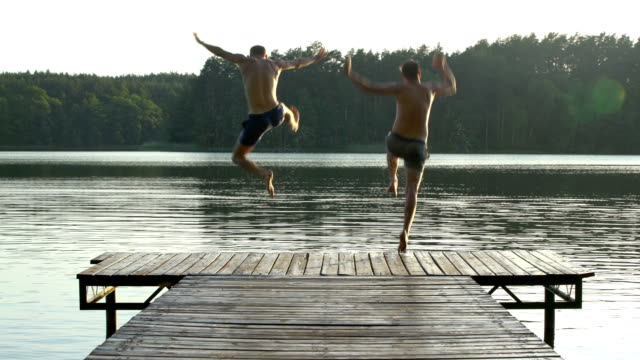 friends jumping into lake. summer activity - jumping stock videos & royalty-free footage