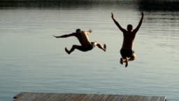 Friends jumping into lake. Summer activity