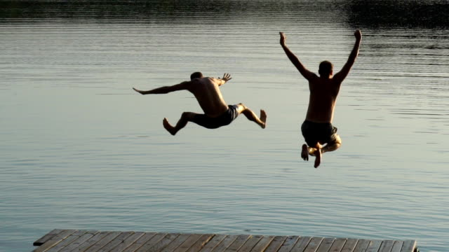 friends jumping into lake. summer activity - shooting baskets stock videos and b-roll footage