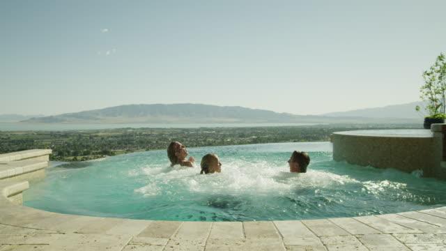vídeos de stock, filmes e b-roll de ws friends (16-19) jumping into pool / cedar hills, utah, usa - lago infinito