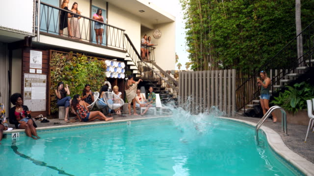 ms friends jumping into pool during party at hotel - 揺らす点の映像素材/bロール