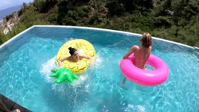 friends jumping into the swimming pool - inflatable stock videos & royalty-free footage