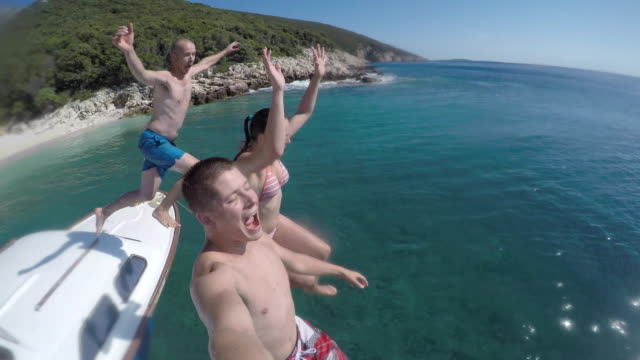 POV Friends jumping off the boat and laughing