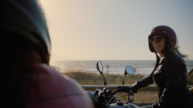 SLO MO. Friends laugh together on motorcycles overlooking the ocean.