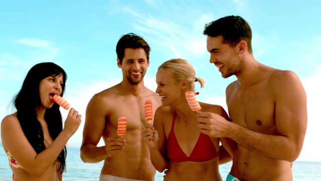 vídeos y material grabado en eventos de stock de friends laughing and eating ice cream on the beach - barba pelo facial