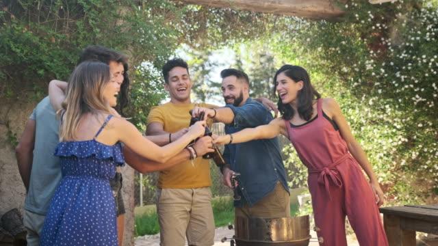 vídeos y material grabado en eventos de stock de amigos riendo e interactuando con barbecuer en la fiesta - terraza