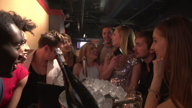 friends laughing and taking pics in nighclub lounge - bucket stock videos & royalty-free footage