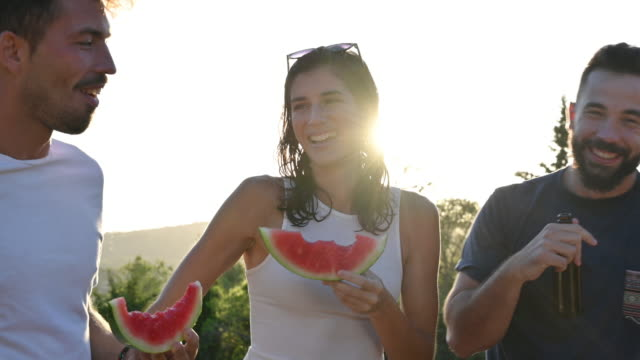 vídeos de stock e filmes b-roll de friends laughing as they eat watermelon at pool party - food and drink