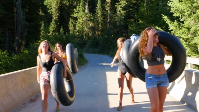 MS Friends laughing while walking across bridge on forest road holding inner tubes on summer afternoon