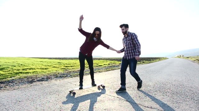 Friends longboard skating on road sunset