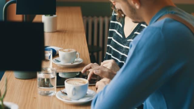 vídeos y material grabado en eventos de stock de amigos mirar tableta digital en la barra - taza de café